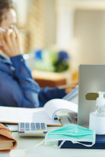 Image: A business owner makes a phone call while working from home. A mask and hand sanitizer are on the desk. View resources for businesses during COVID-19.