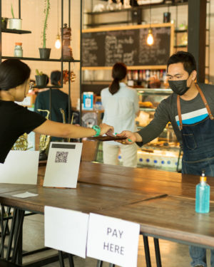Image: a restaurant employee wearing a mask as he takes an order. Learn how you can pivot your restaurant in the wake of Coronavirus.